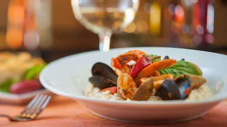 A dish of risotto topped with clams, mussels, shrimp, basil and roast pepper