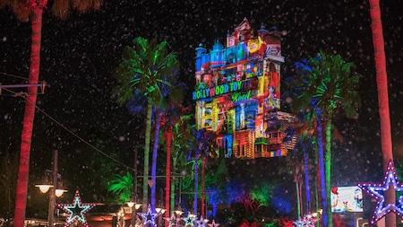 Hollywood Tower Hotel con proyecciones de juguetes sobre su fachada, cerca de palmeras y luces en forma de estrellas