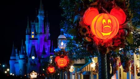 Luminosas farolas de calabaza con el diseño de Mickey Mouse adornan las calles afuera del Cinderella Castle