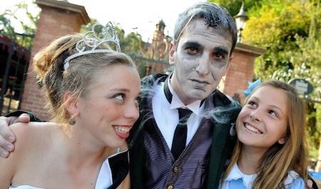 Tres Visitantes adolescentes parados hombro con hombro y con disfraces de princesa, del fantasma presentador de Haunted Mansion y de Alice in Wonderland