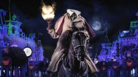 De noche, durante Mickey's Not So Scary Halloween Party, Headless Horseman sentado sobre un caballo mientras sostiene una calabaza de Halloween en llamas.