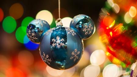 Un adorno navideño con forma de orejas de Mickey cuelga de un árbol de Navidad decorado
