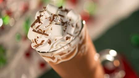 A tall glass of hot chocolate topped with whipped cream at Mickey's Very Merry Christmas Party