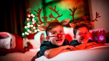 Dos niños disfrutan una sorpresa navideña en su habitación de hotel de Disney
