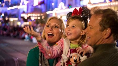 Un père, une mère et leur fille regardent avec émerveillement la neige qui tombe autour d'eux sur Main Street, U.S.A.