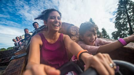 A mother and her daughter enjoying an excited ride aboard the Seven Dwarfs Mine Train in Fantasyland