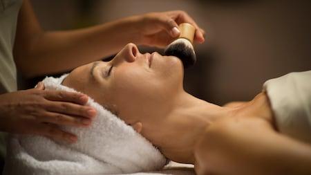 Una Visitante con una toalla en la cabeza y los ojos cerrados disfrutando de una relajante experiencia en un spa