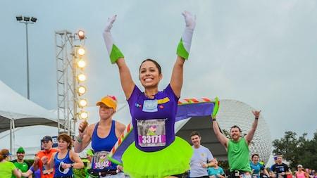 Una corredora con un disfraz de la temática Buzz Lightyear levanta los brazos victoriosamente durante una carrera de runDisney