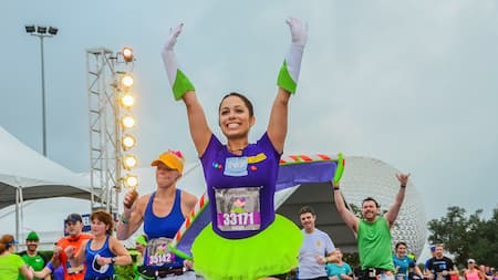 A runner in a Buzz-Lightyear-themed costume holding her arms up victoriously during a runDisney race