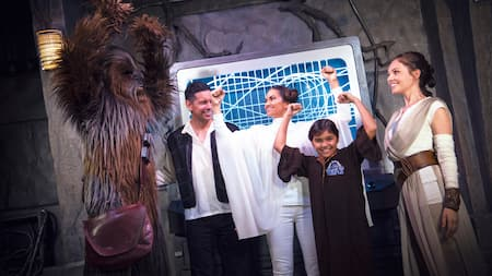 A family dressed in Star Wars costumes poses with Chewbacca and Rey