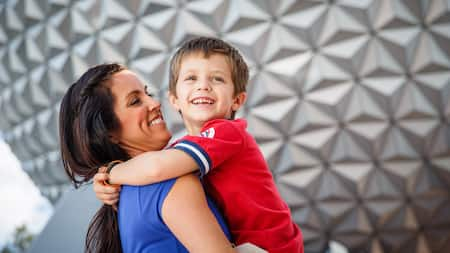 A woman holds a smiling boy in front of Spaceship Earth