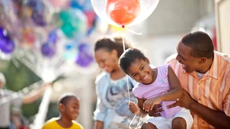 A smiling girl holds a balloon as her father picks her up