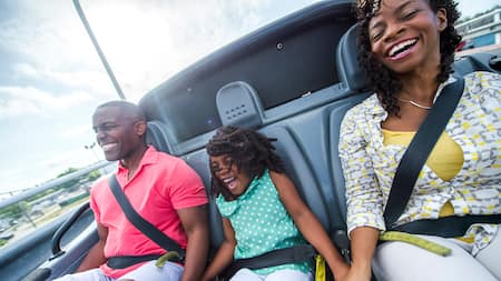 A woman, a man and a girl smile on a roller coaster