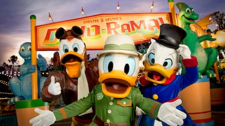 Launchpad McQuack, Donald Duck and Scrooge McDuck stand in front of a sign that reads Chester and Hester's Dino Rama