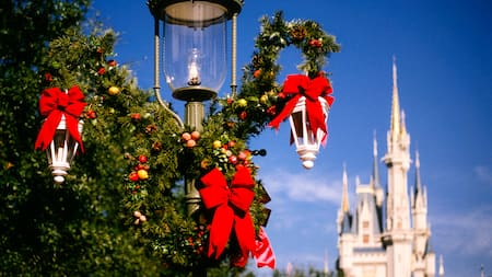 close up of a lamppost festooned with red holiday ribbons and greenery with cinderella castle