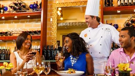 Tres comensales y el chef Phillip ríen juntos en The Chef's Domain en Citricos