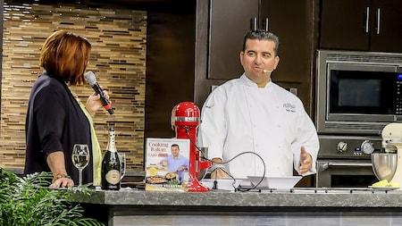 Una mujer con un micrófono se dirige al chef Buddy Valastro en una cocina de demostración que contiene una y uno de los libros de cocina del chef.
