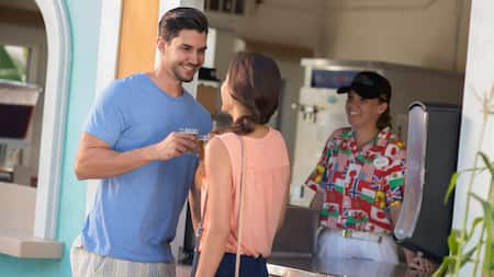 A man and woman smile at each other while holding beverages in front of a concession stand