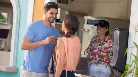 Un hombre y una mujer se sonríen mientras sostienen sus bebidas frente a un puesto de comida