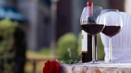 A rose laying on a marble counter alongside 2 glasses of wine and a wine bottle