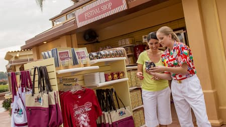 A sales clerk shows an item to a mother and daughter at the Festival Shop at Epcot