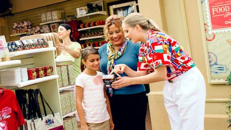 A sales clerk and a female Guest marvel over a gift item at the Festival Shop at Epcot
