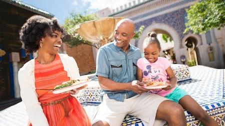 3miembros de una familia joven sonríen mientras están sentados al borde de una fuente en un jardín, rodeados platos de comida marroquí.