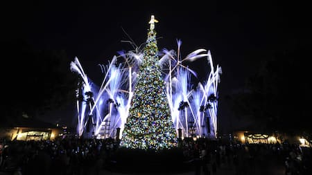 A tree decorated with Christmas lights and topped by an angel near a crowd of people, trees and fireworks