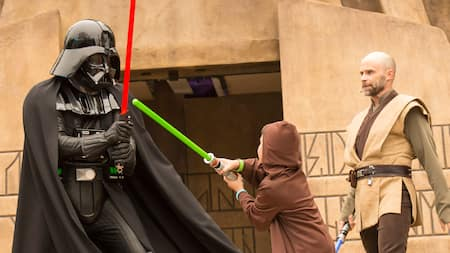 A young boy in a Jedi costume engaging in toy life saber play with the Darth Vader Character