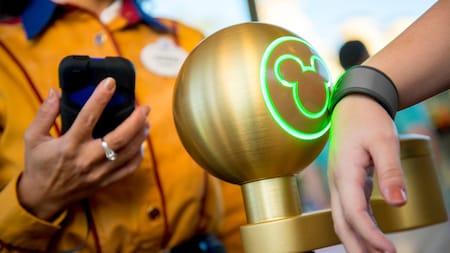 Um Visitante toca sua MagicBand no ponto de contato de uma atração ao lado de um funcionário da Disney