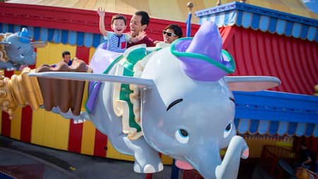 A mother, father and young son smile while riding Dumbo the Flying Elephant at Magic Kingdom park