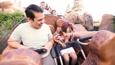 Uma menina e o pai se seguram firme a bordo da emocionante atração Seven Dwarfs Mine Train