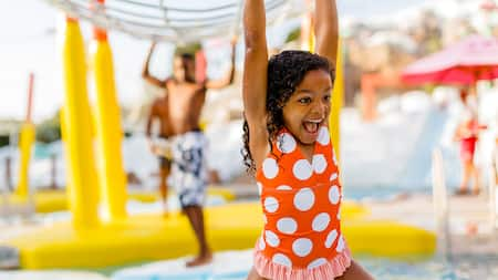 A young girl smiles excitedly while splashing about in a water play area at a Disney Resort hotel