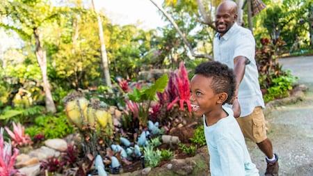 Un enfant souriant tient le bras d'un adulte en marchant à Pandora The World of Avatar