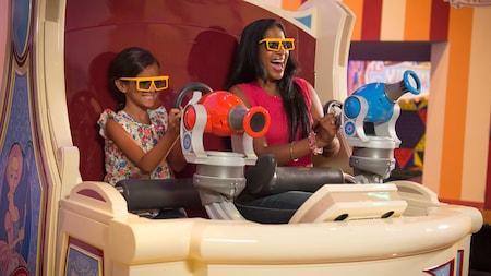 Uma mulher e uma menina sorriem se divertindo na atração Toy Story Midway Mania!
