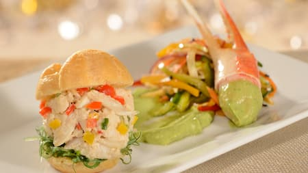 A slider stuffed with crab meat and bell peppers next to a crab claw, fried vegetables and guacamole