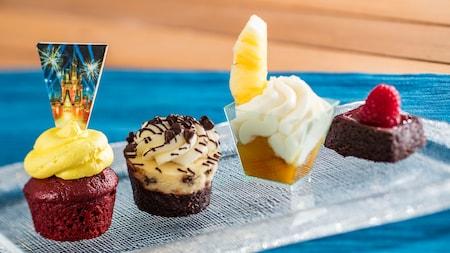 Un cupcake, un muffin, un brownie y fruta con crema en una taza