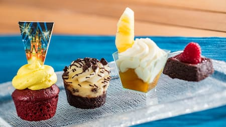 A cupcake, a muffin, a brownie and fruit and cream in a cup