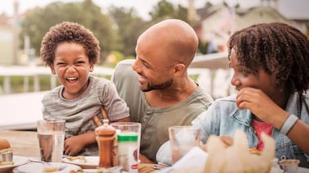 A family smiles while seated at a table