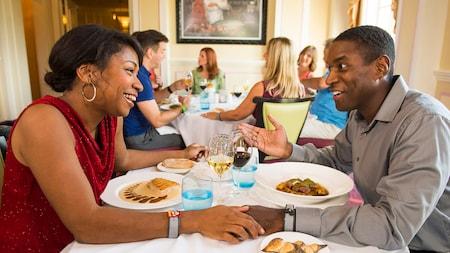 Um casal conversa a uma mesa de um restaurante movimentado