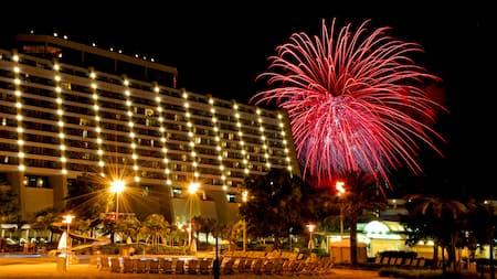 The pool area at Disneys Contemporary Resort illuminated at night with a view of the fireworks