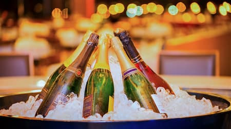 Bottles of champagne lean together in a large bucket of ice waiting to be uncorked