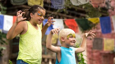 Uma jovem Visitante e seu irmão mais novo sorriem enquanto posam com uma pintura facial feroz