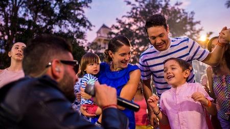 Um cantor canta ao microfone e um menino dança sob os olhares da família