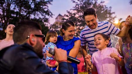 Un muchacho canta con un micrófono y un niño baila al ritmo de la canción mientras su familia observa