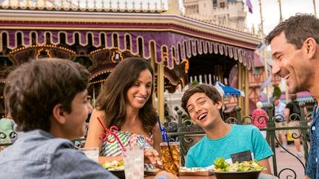 2niños, varón y mujer, preadolescentes y sus padres se ríen mientras almuerzan cerca de un carrusel