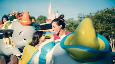 A mother and daughter ride Dumbo the Flying Elephant