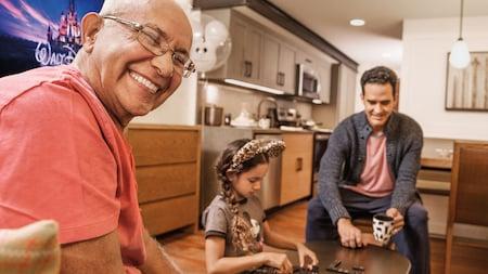2 hombres sonríen y juegan al dominó con una niña que tiene orejas de Mickey