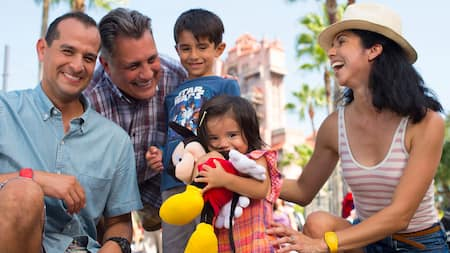 Una familia sonriente agachada cerca de una niña que sostiene un peluche de Mickey Mouse