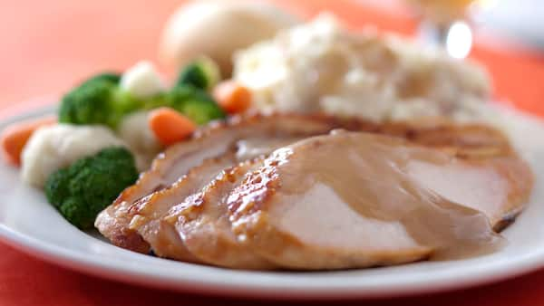 Sliced chicken breast topped with gravy next to mashed potatoes, cauliflower, carrots and broccoli